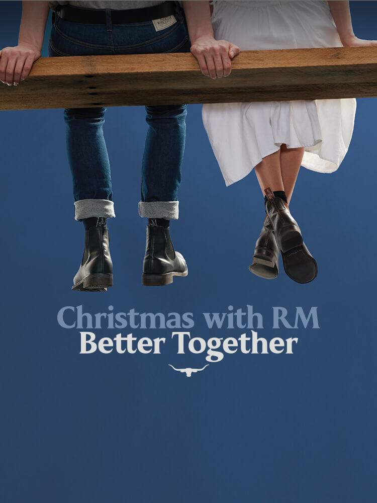 R.M.Williams Christmas graphic legs dangling with RM boots on